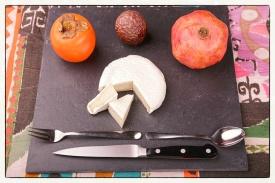 zwei Ecken mit einer Sharon-Frucht, einer Maracuja und einem Granatapfel